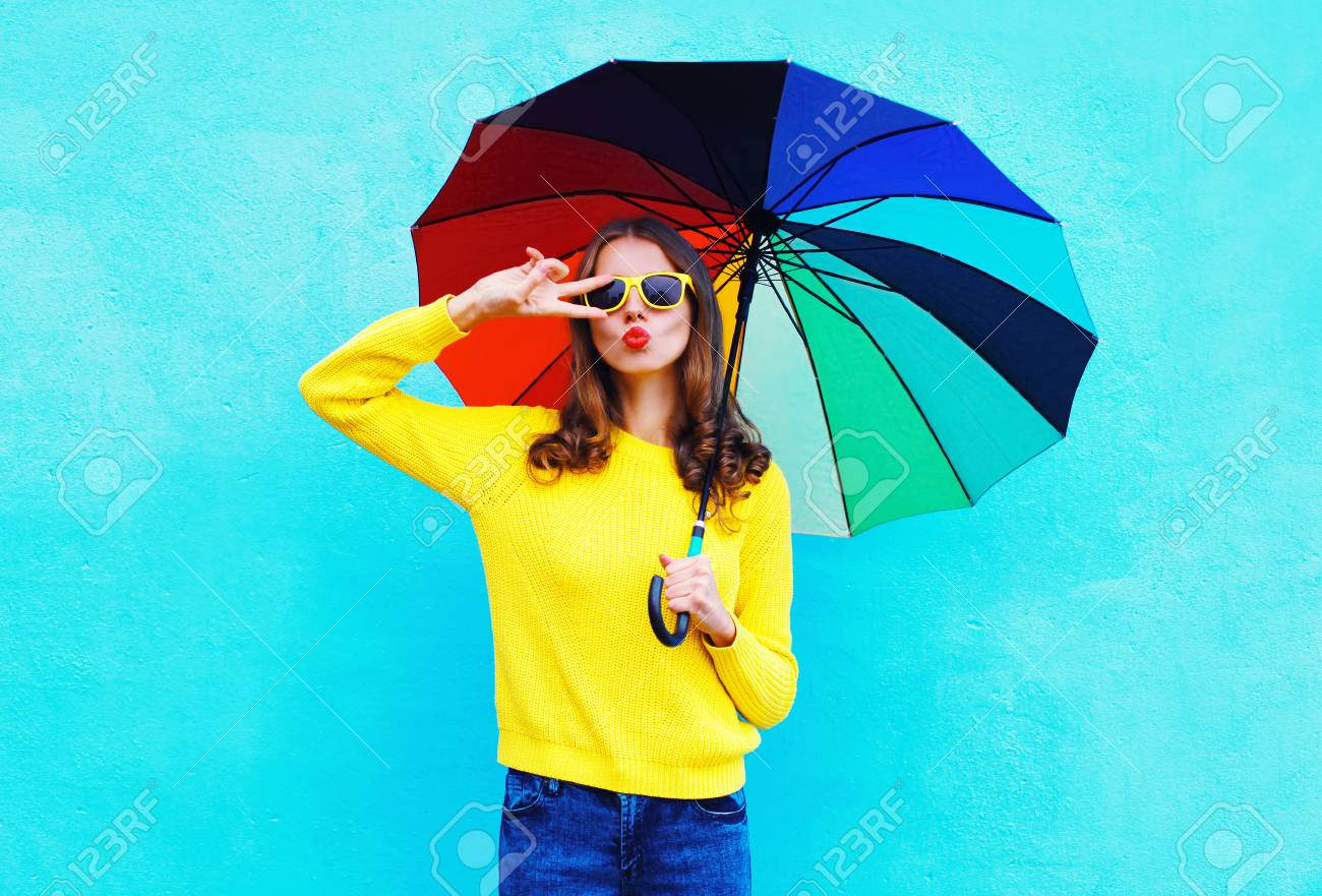 Fashion pretty cool woman holding colorful umbrella in autumn day over blue background wearing a yellow knitted sweater - 63469295
