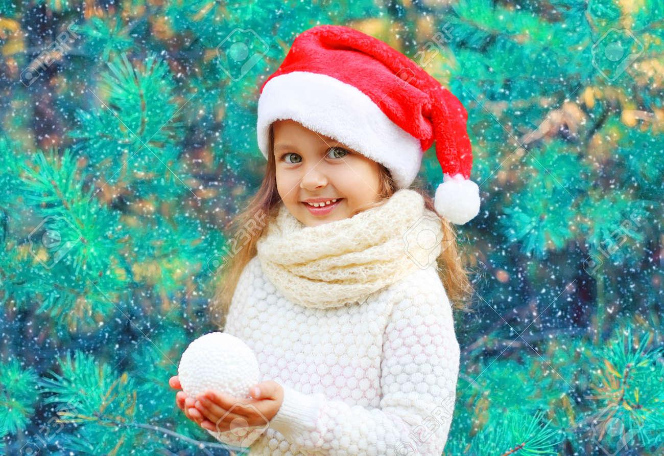 Foto de archivo - Retrato de Navidad niño sonriente niña en el sombrero  rojo de bola de nieve de retención cerca de un árbol de la ramificación 80d6a653dca