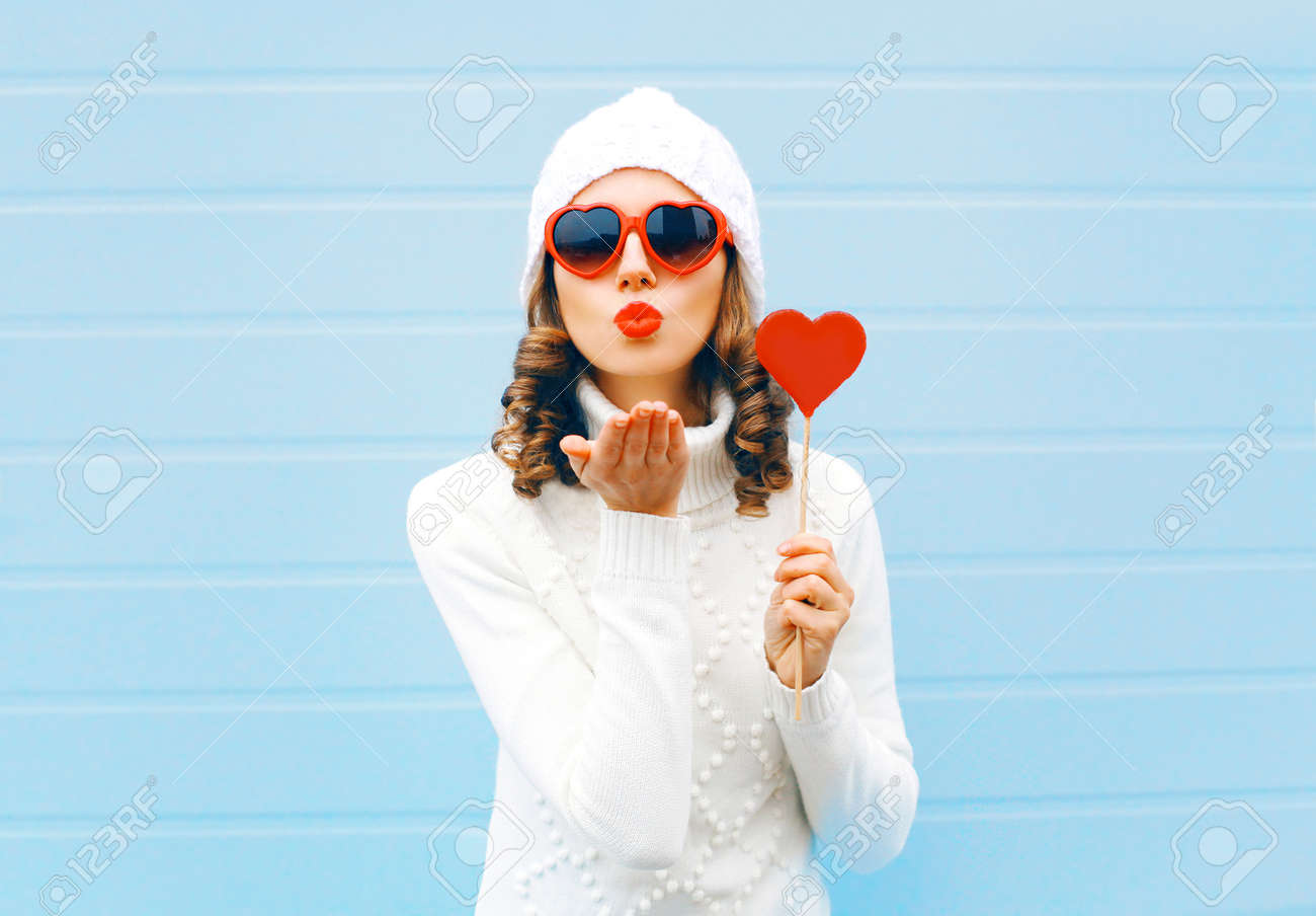 Portrait pretty woman blowing red lips sends air kiss holds lollipop heart wearing a heart shape sunglasses, knitted hat, sweater over blue background Stock Photo - 68211889
