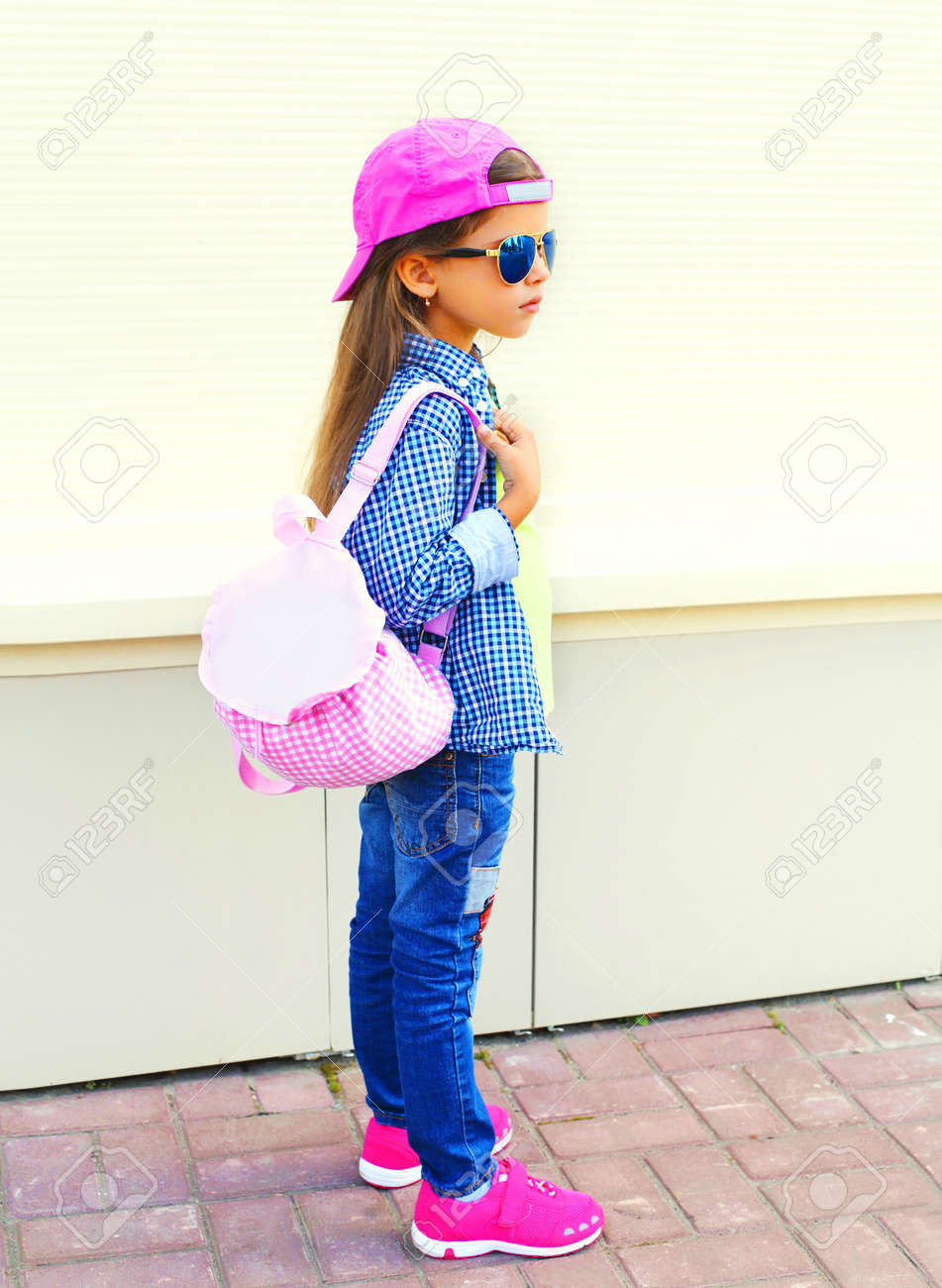 Fashion kid little girl wearing a baseball cap and backpack in the city on  a white ae622af3aee
