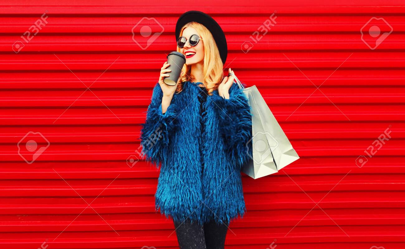 Portrait stylish smiling woman drinking coffee holding shopping bags wearing blue faux fur coat, black round hat and sunglasses posing over red wall background - 136682908