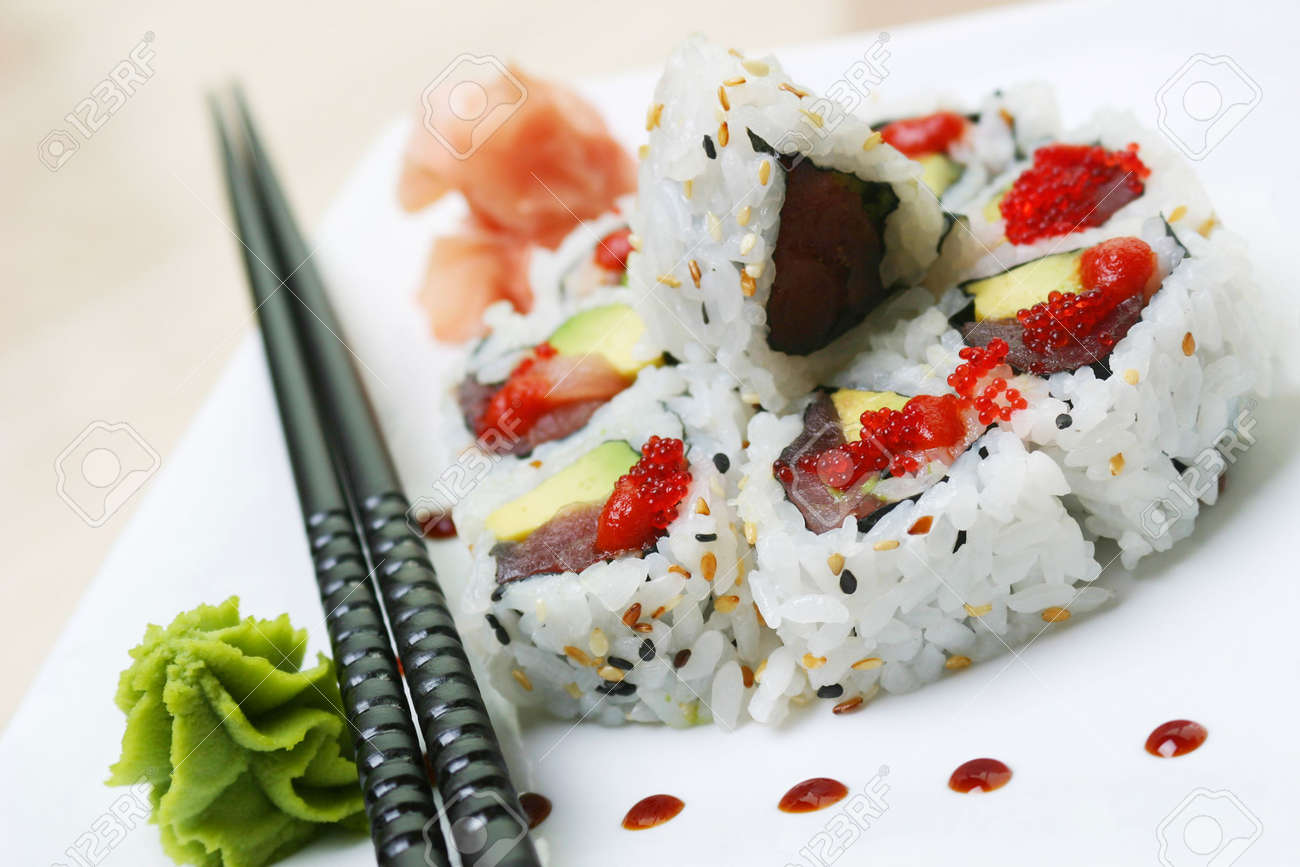 Crab, fresh avocado and cucumber, rolled inside out in nori seaweed, sprinkled with sesame seed and topped with tobikko. Shallow DOF. Stock Photo - 220354