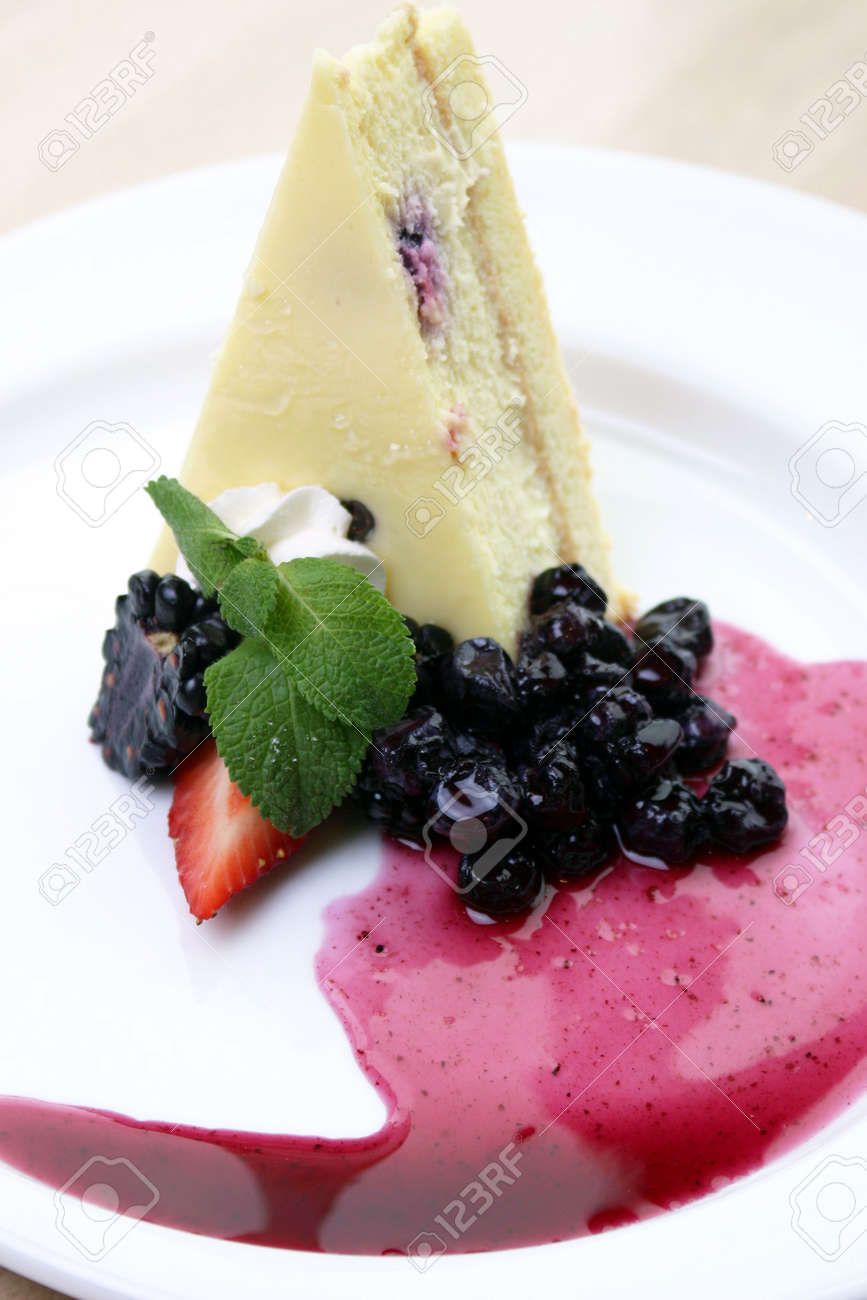 Wildberry cheesecake served with raspberry puree and wildberries. Shallow DOF. Stock Photo - 220363