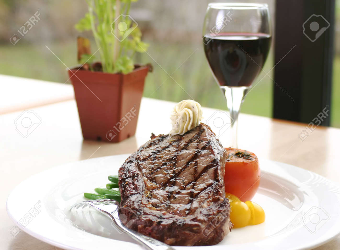 12oz ribeye steak topped with truffle butter and grilled tomato. Served with red wine. Stock Photo - 220565