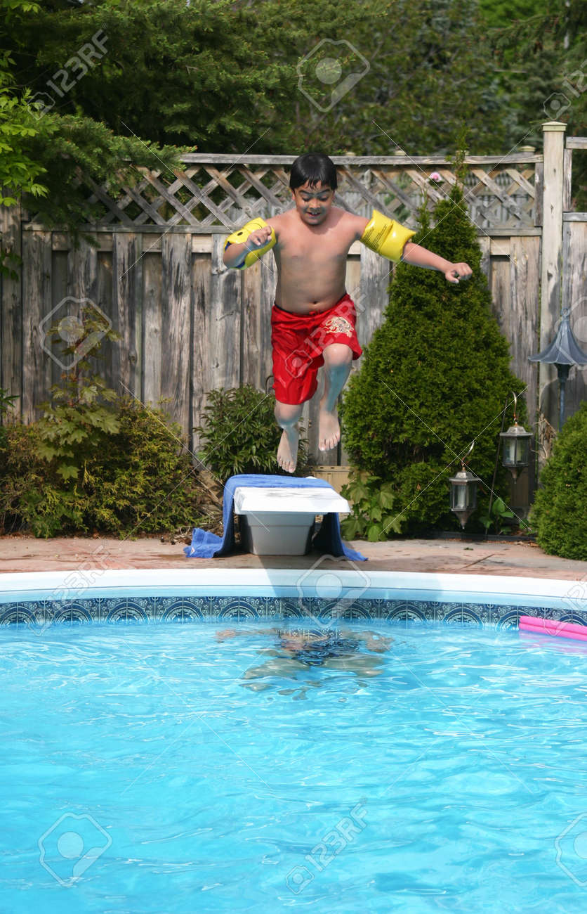 Young boys jumps into the swimming pool from a diving board.