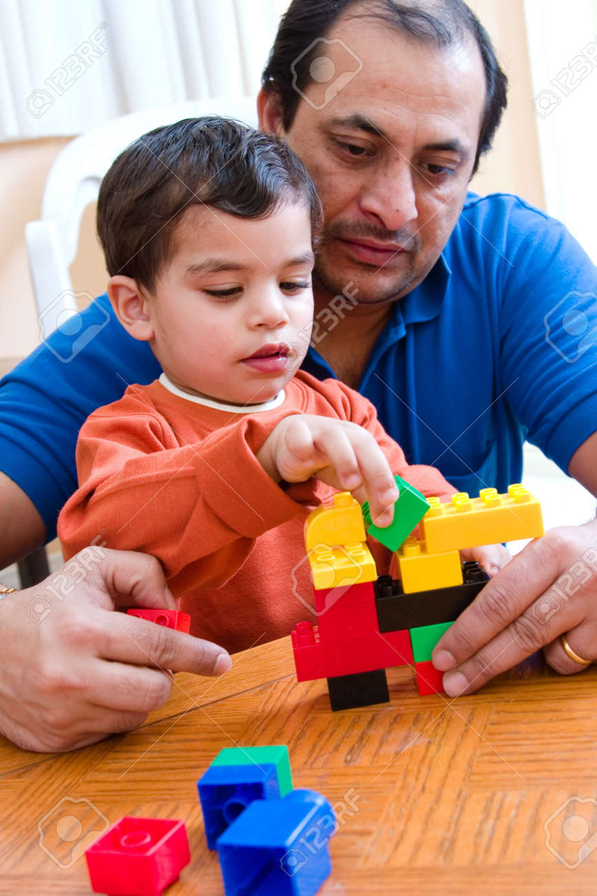 A father plays with his son and helps him build with his blocks Stock Photo - 1180424