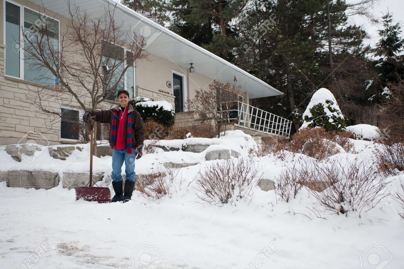 a young east indian man shovels snow outside his house stock photo