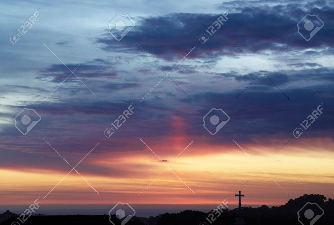 Silhouette of the holy cross on background of storm clouds stock - Holy Day Sunset Sky With The Silhouette Of A Cross Breaking The Horizon