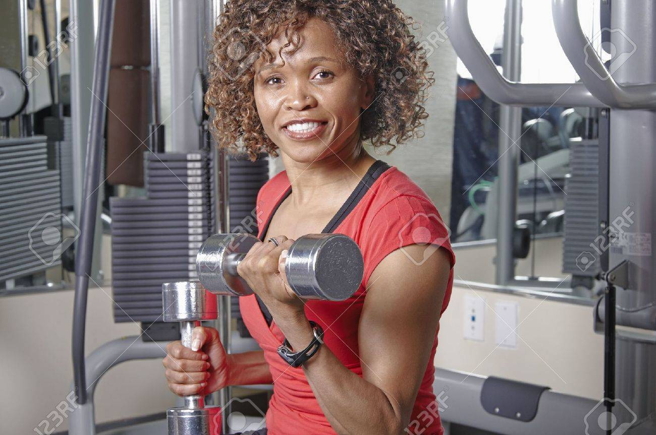 African American woman doing bicep curls in a gym Stock Photo - 6675424