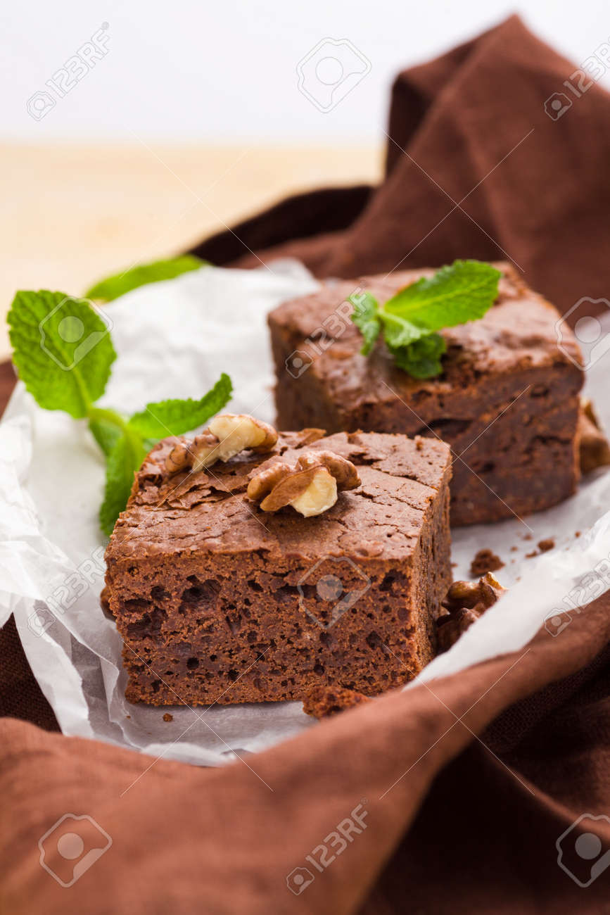 Brownie Sweet Chocolate Dessert With Walnuts And Meant Leaves