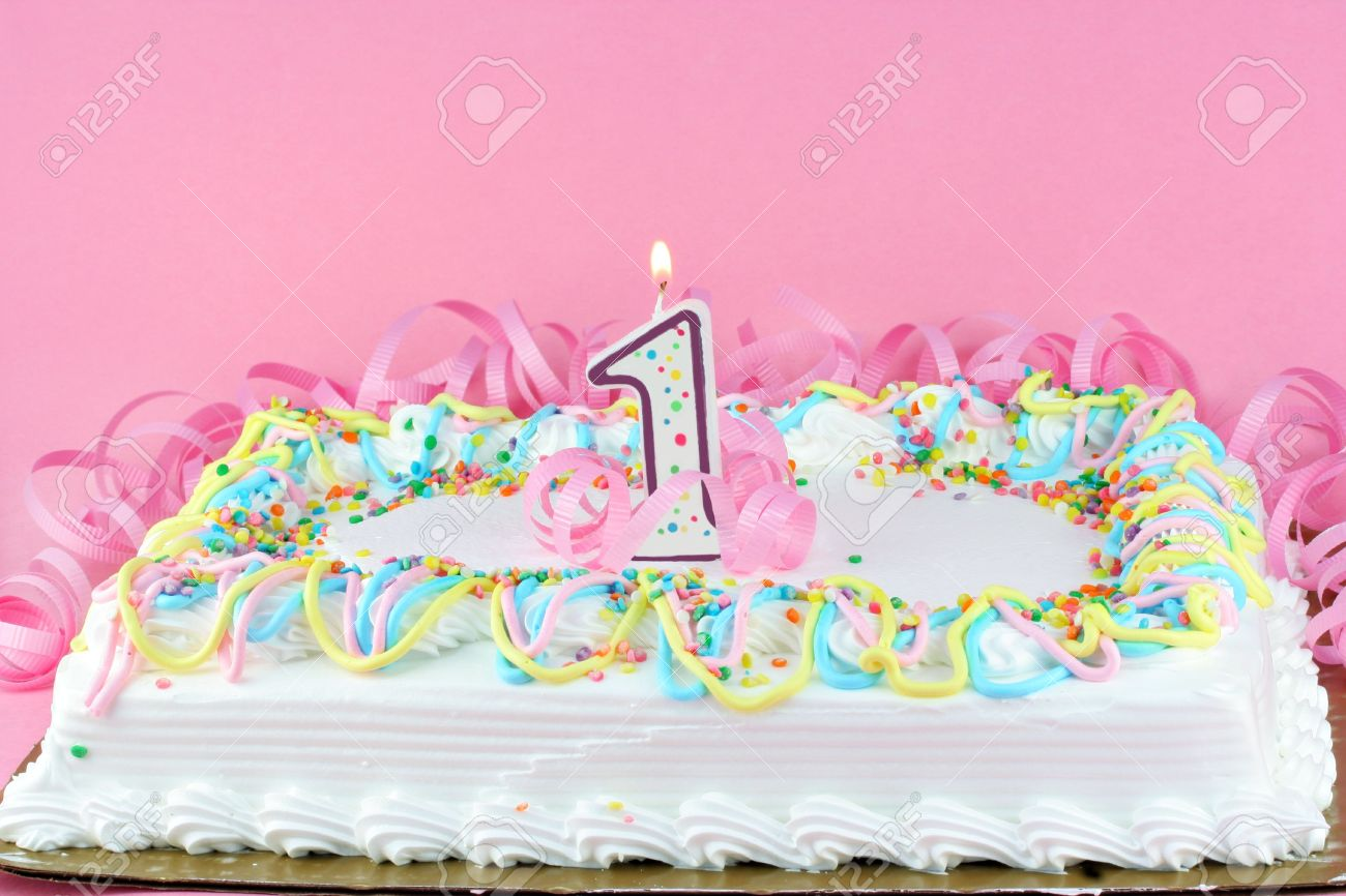 One White Frosted And Decorated Sheet Cake With Lit Candle Pretty Pink Background