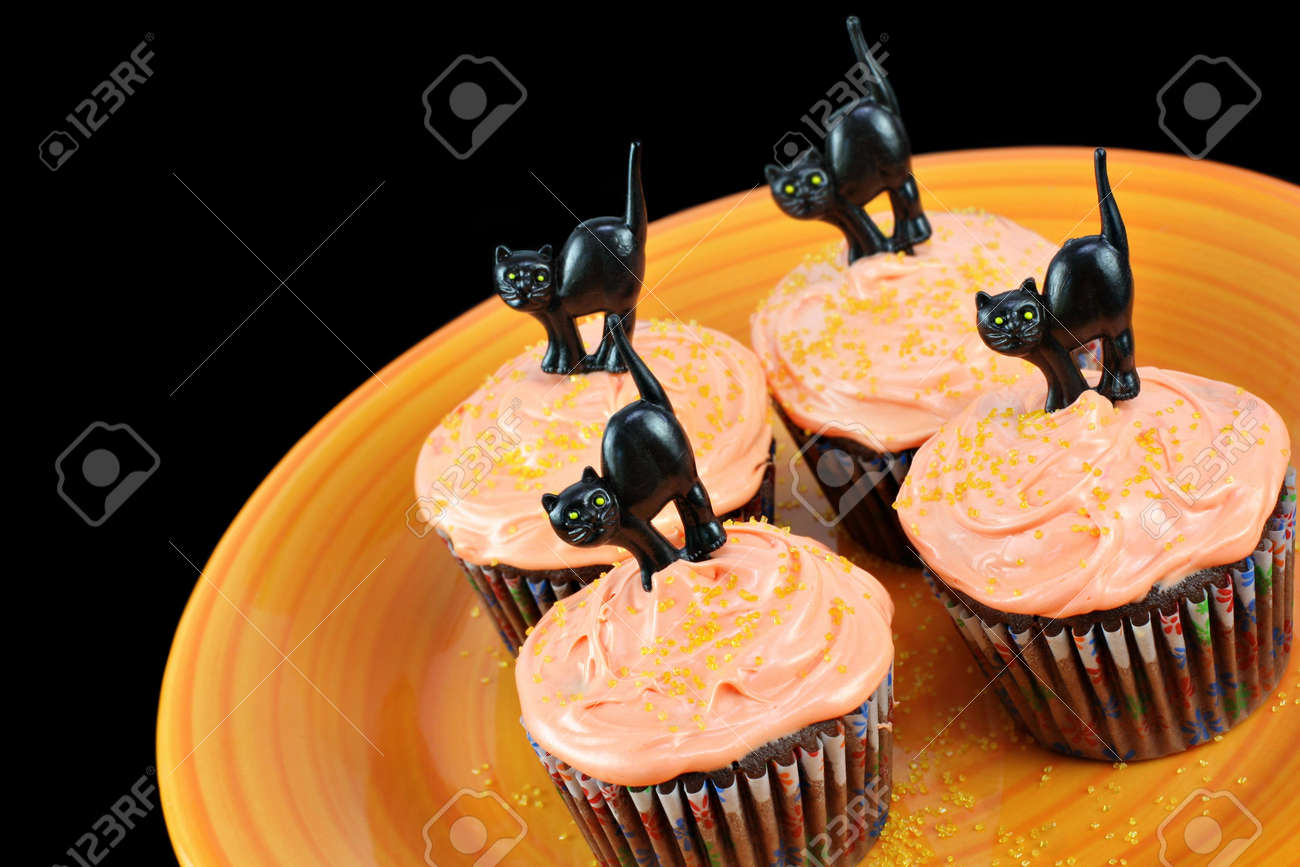 halloween cupcakes chocolate cupcakes with peach frosting on an orange plate decorated for halloween with - Halloween Decorated Cupcakes