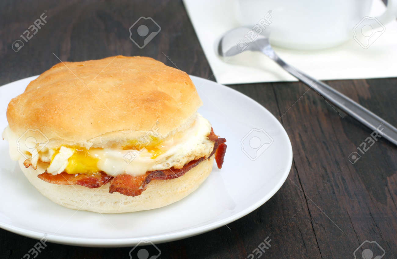 Fresh bacon and egg biscuit on a rustic wooden table. Stock Photo - 7076398