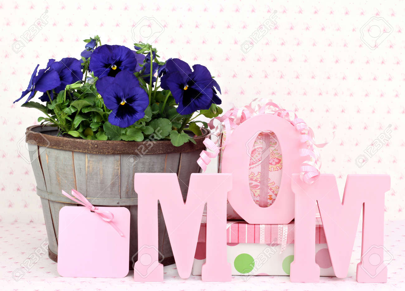 Beautiful pansys in a rustic basket, gifts, a gift card and Mom spelled out in wooden letters.  Great for Mom's birthday or Mothers Day. Stock Photo - 9440954