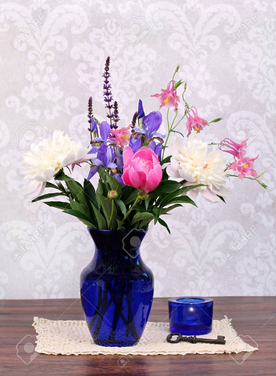 An assortment of typical and beautiful spring flowers in a navy an assortment of typical and beautiful spring flowers in a navy vase with candle and antique izmirmasajfo