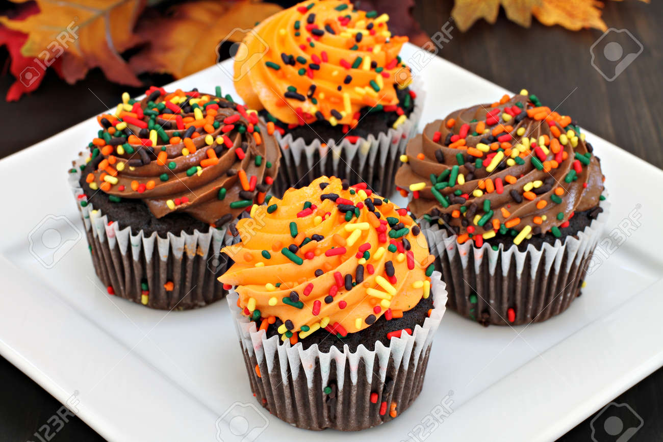 Four Chocolate Cupcakes Frosted In Chocolate And Orange With Stock