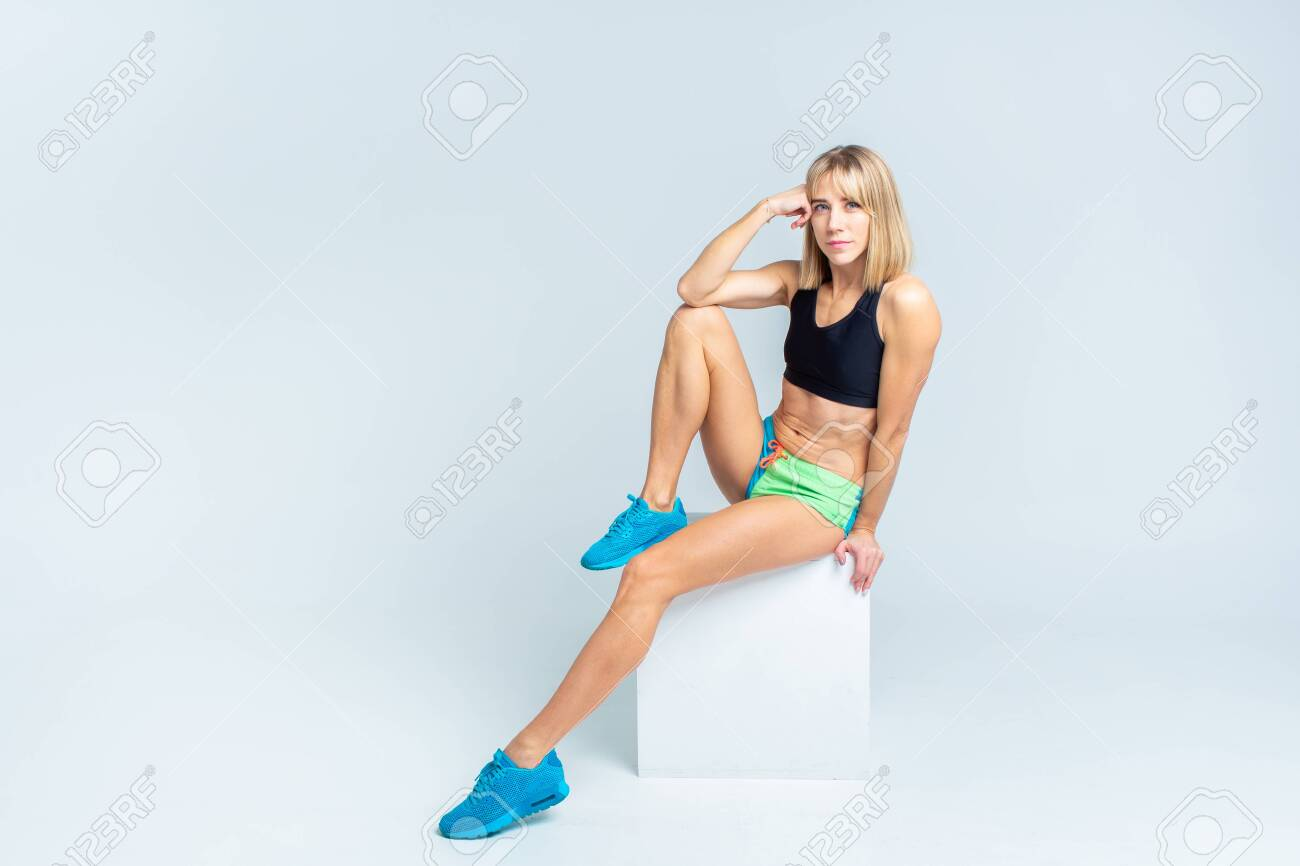 Portrait of beautiful athletic caucasian woman in sport bra and shorts sitting on a white cube on a white studio backgroung. Copyspace - 144199186