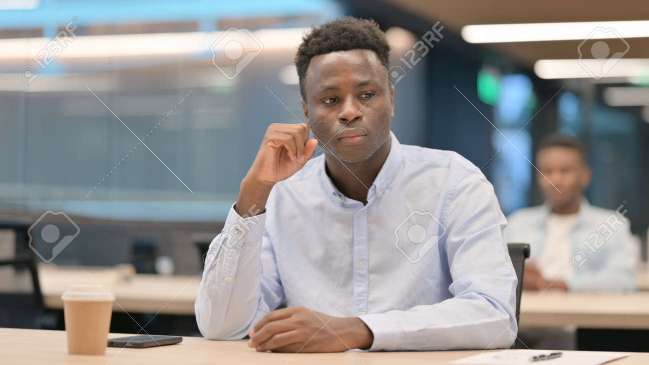 African Businessman Sitting in Office Thinking - 169391046
