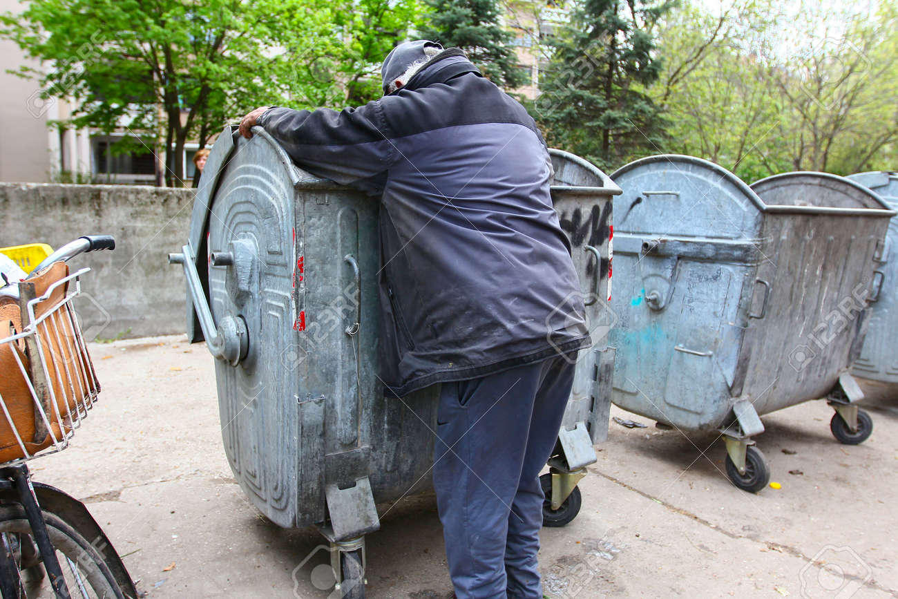 A homeless man looking for food in a garbage dumpster - 18258976