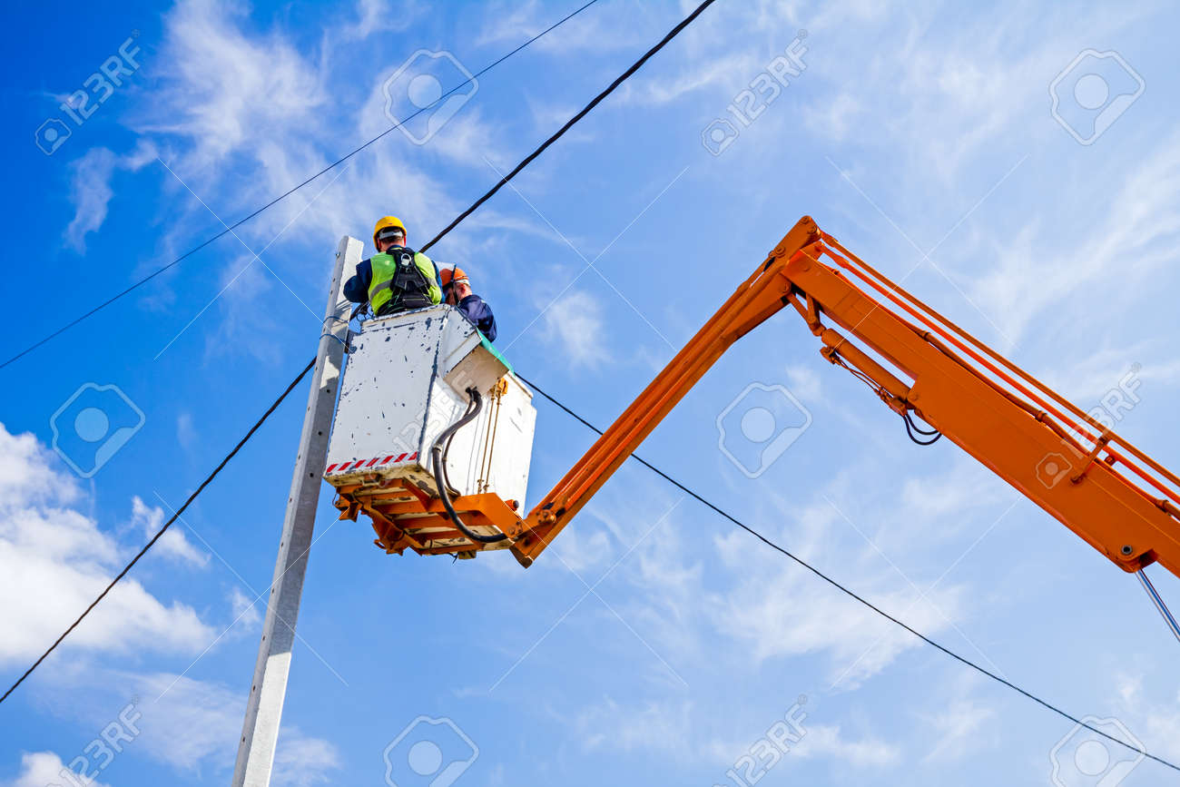 Technician works in a bucket high up on a power pole. - 38195073
