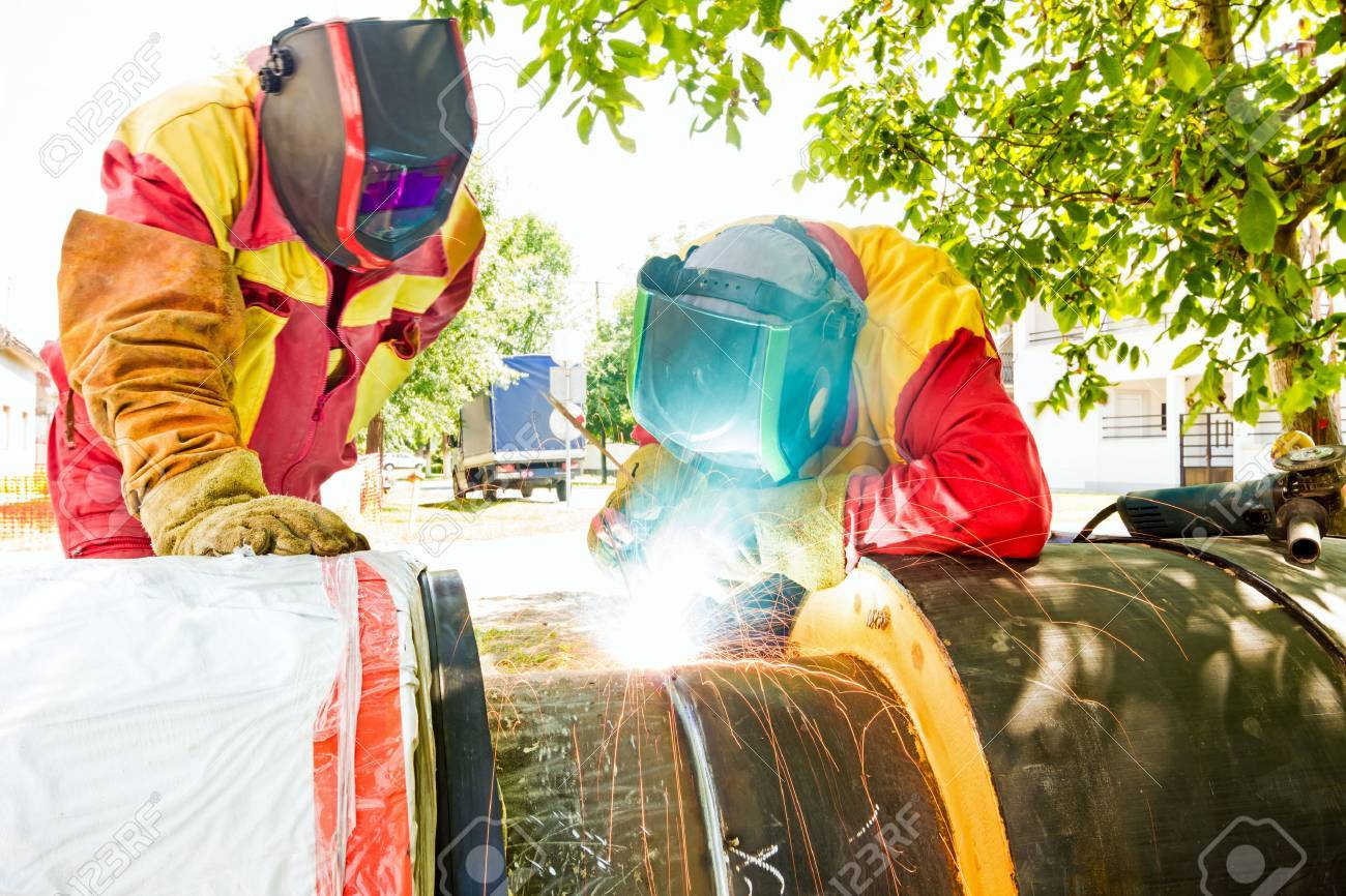 Welder working on a pipeline in construction site wearing overall and safety equipment - 38912520