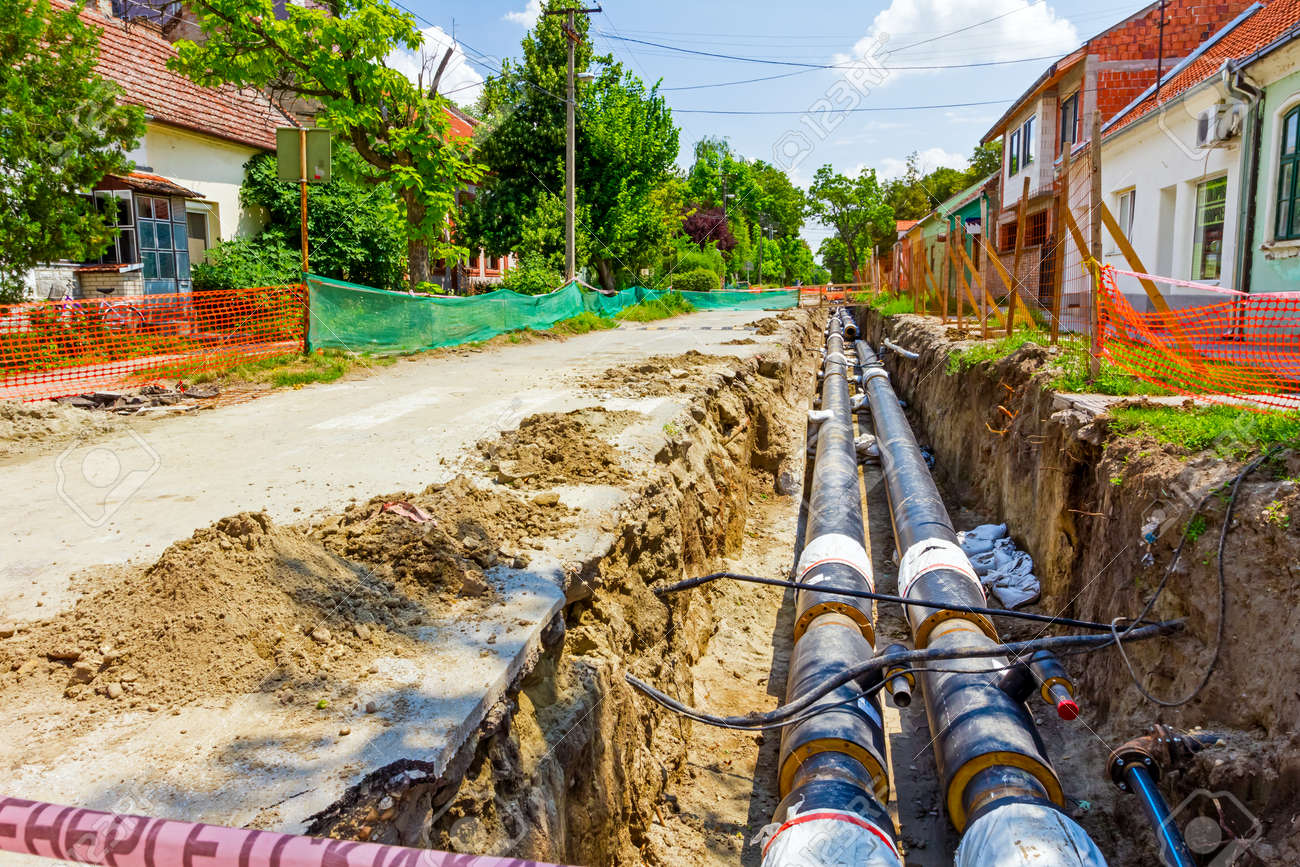 Long earth excavation for new pipeline is protected by iron shuttering. - 38912721