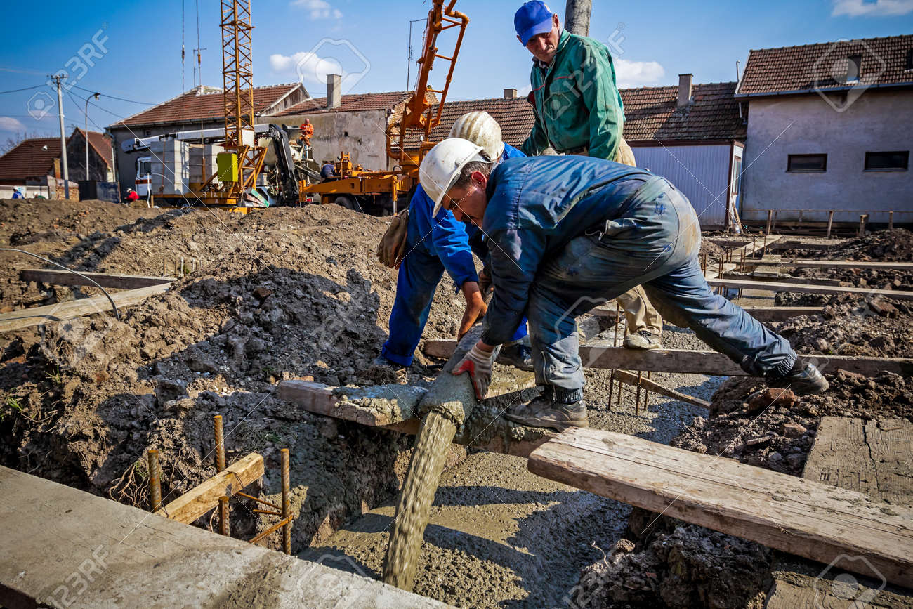 Construction workers are pouring concrete in building foundation, directing the pump tube on right direction. - 47775448