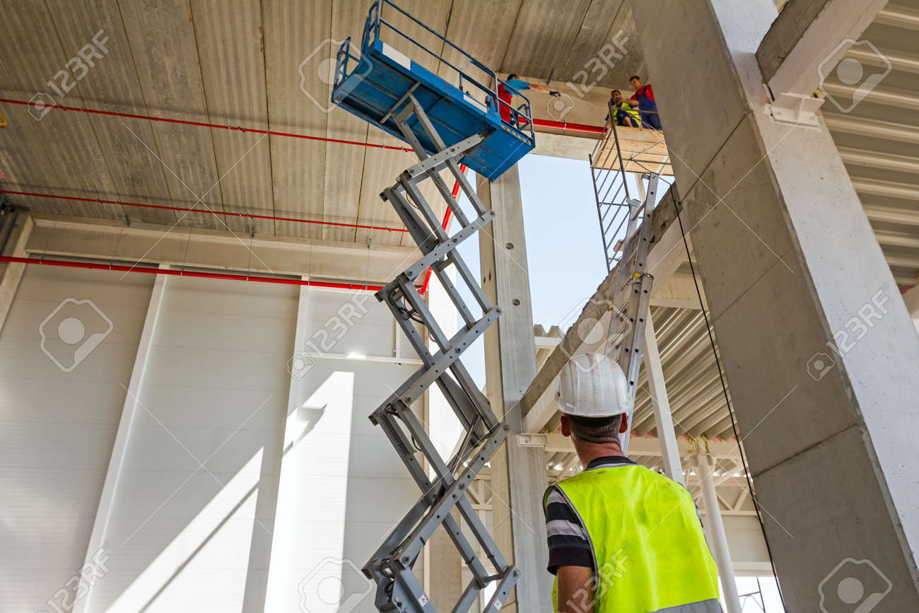 Boss control workers in scissor lift platform on a construction site. - 55381788