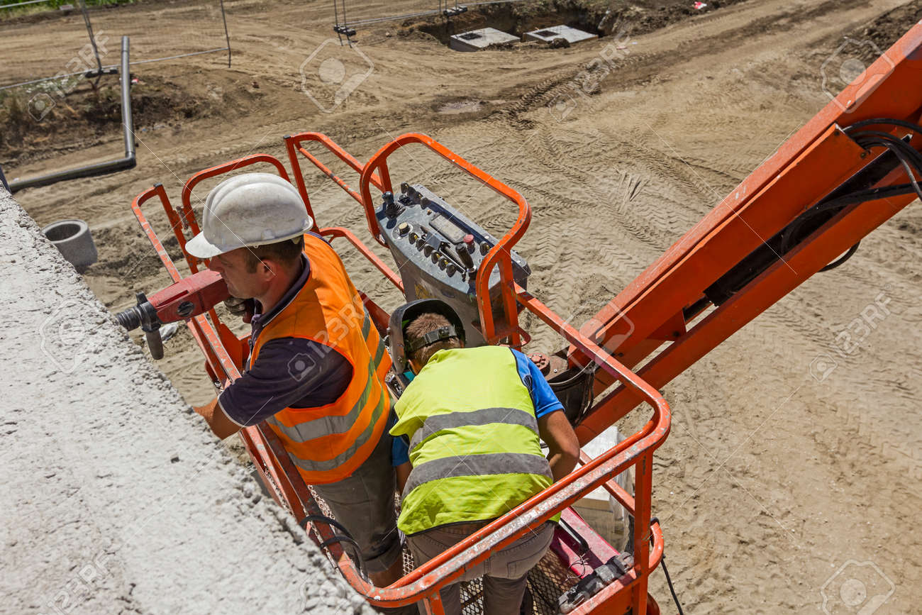 High elevated cherry picker with team of workers on construction site. - 55391580