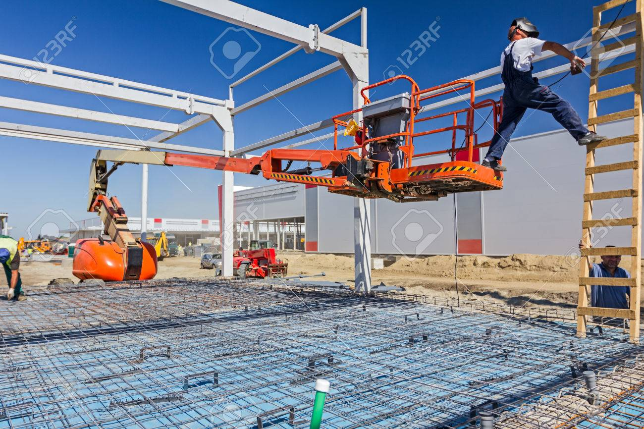 Construction worker is welding metal frame without proper safety equipment on wooden leaders. - 55391586