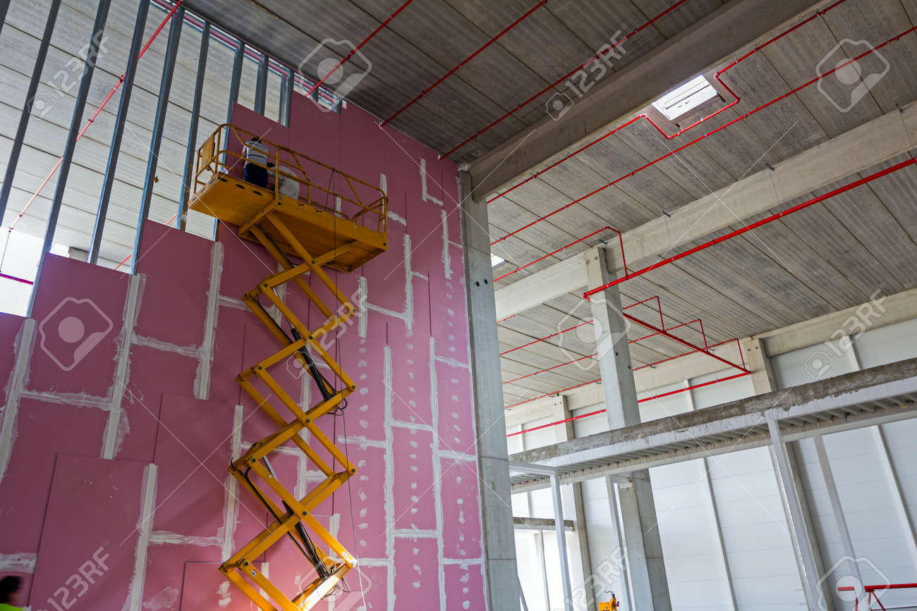 Workers are high up in cherry picker on building site. - 55414546