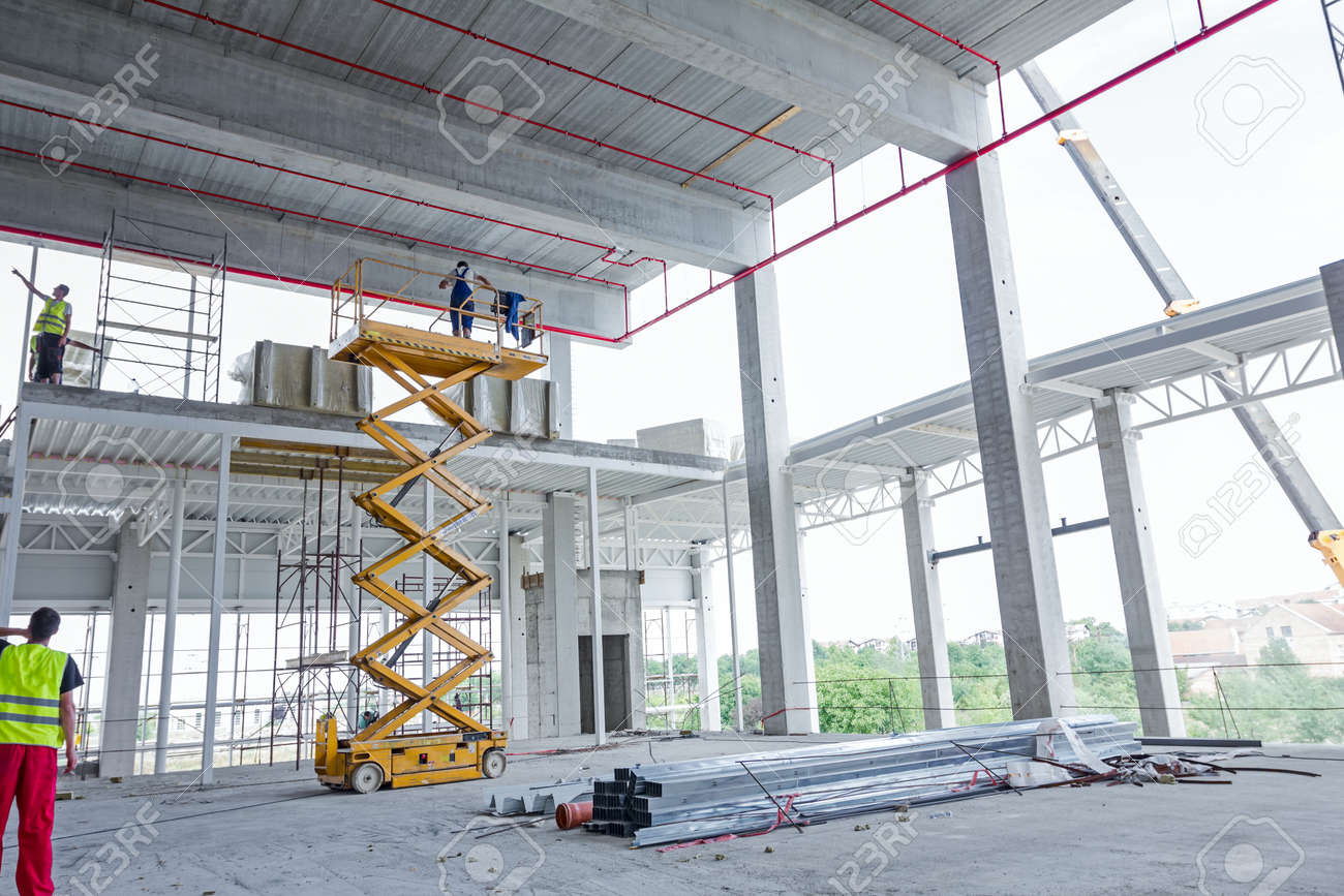 Workers are high up in cherry picker on building site. - 55419963
