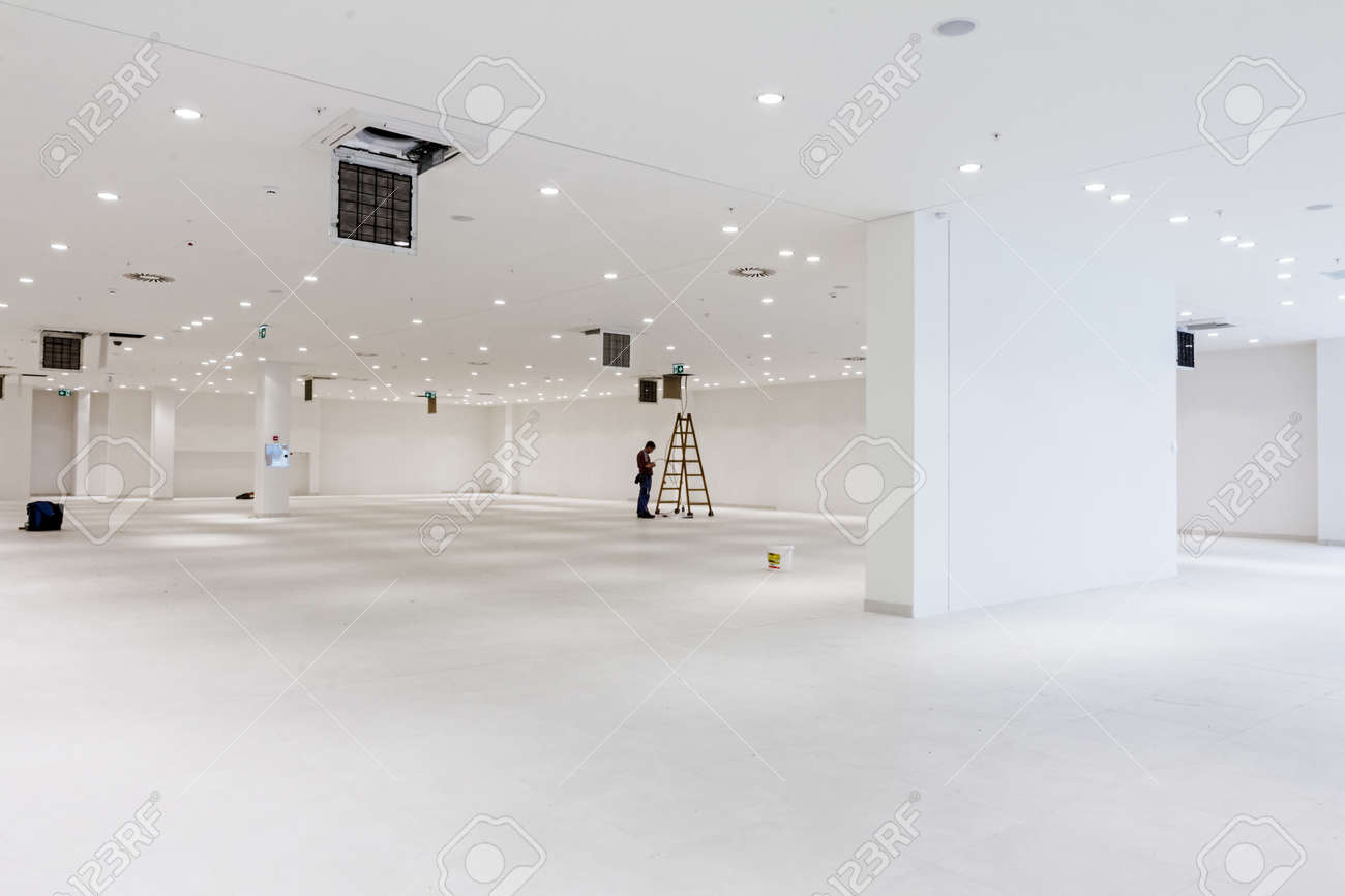 Workers are used wooden ladder to complete conditioning system ventilation at modern office ceiling with air duct and lamps. - 57211245