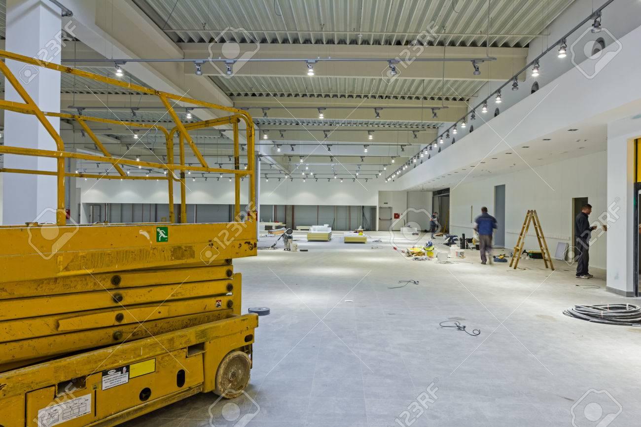 Scissor lift platform is inside of new big hall in building process. - 57209184