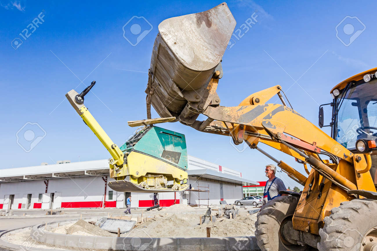 Excavator is moving over building site with raised up front bucket,