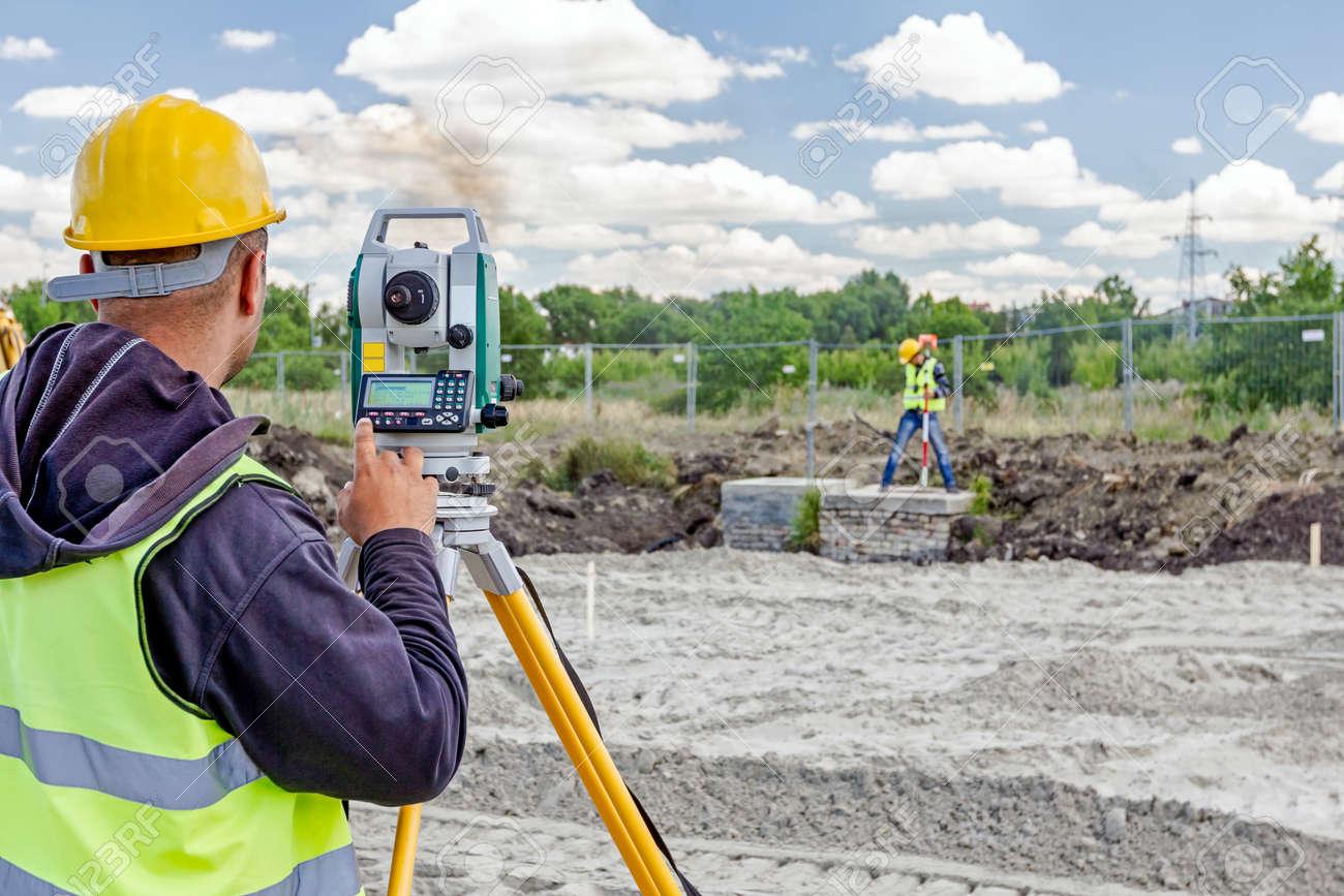 Surveyor engineer is measuring level on construction site. Surveyors ensure precise measurements before undertaking large construction projects. - 63172531