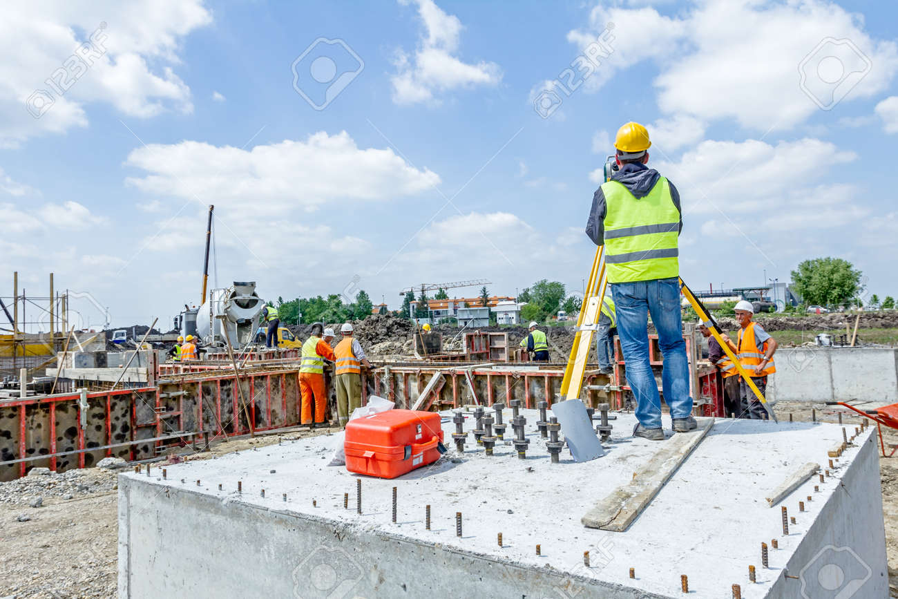 Zrenjanin, Vojvodina, Serbia - May 25, 2015: Surveyor engineer is measuring level on construction site. Surveyors ensure precise measurements before undertaking large construction projects. - 71466852
