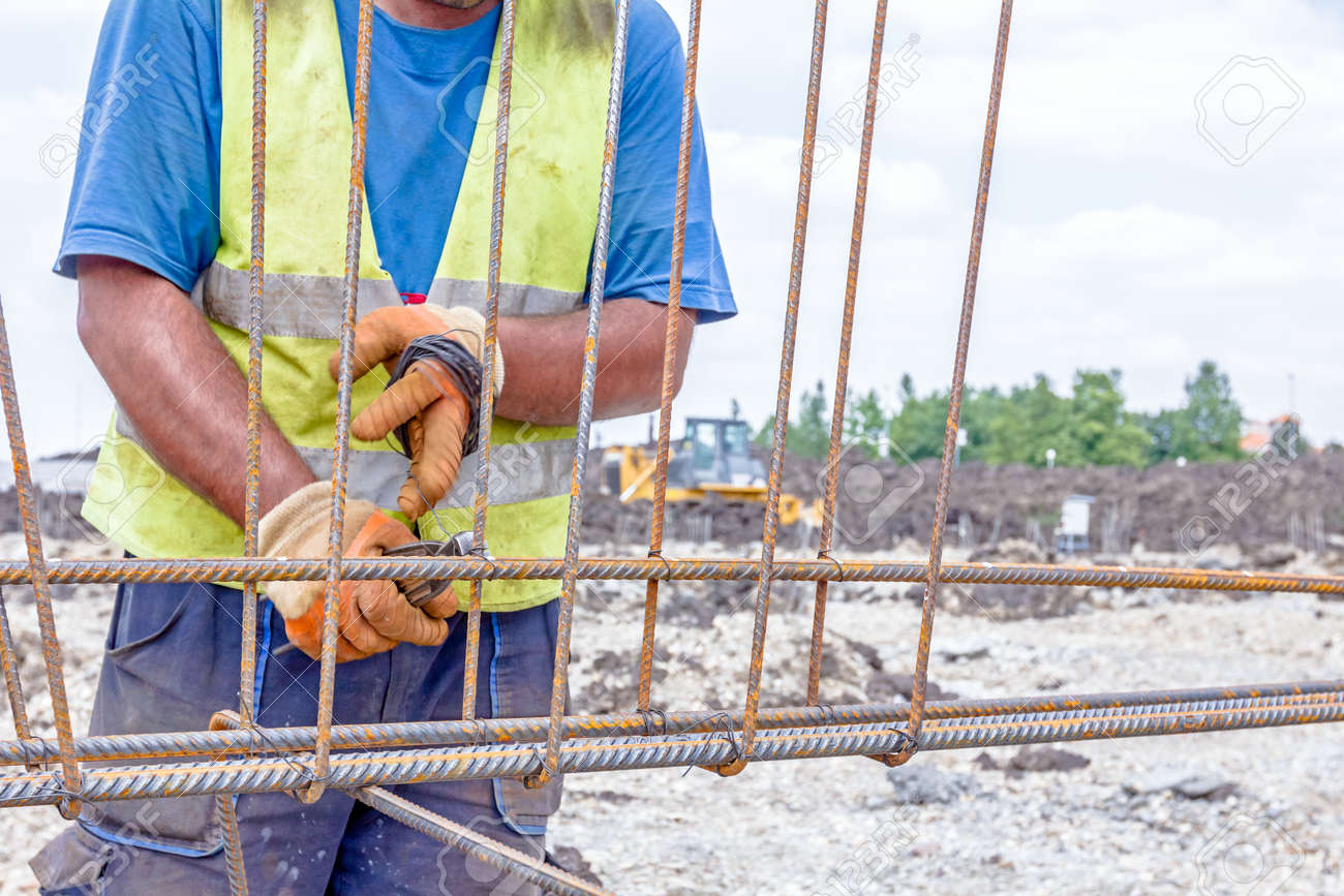 stock photo worker is tying rebar to make a newly constructed footing frame binding concrete frame