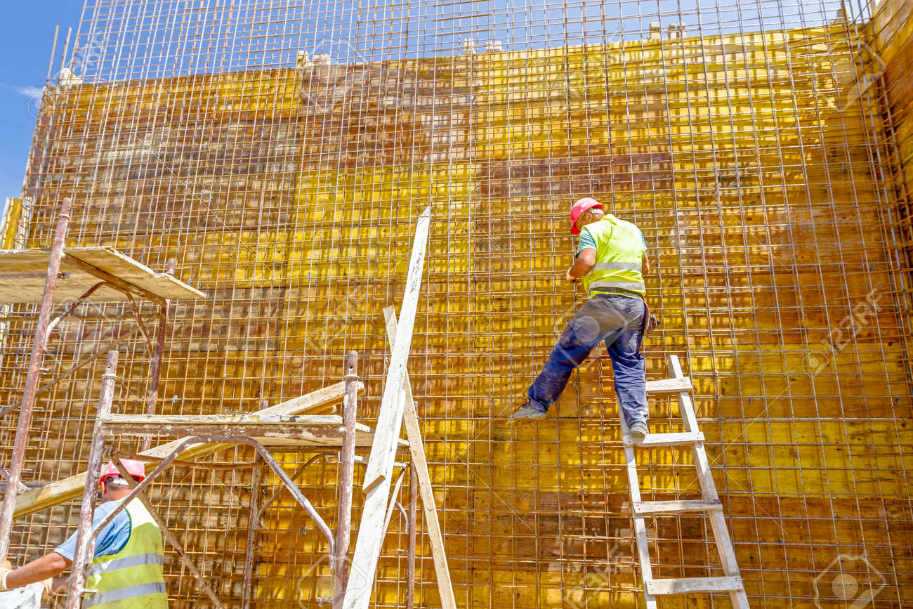 Construction worker is binding rebar for tall reinforced concrete construction at the building site. - 76976800