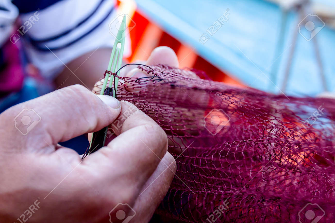 Needle with thread in fisherman hands repairing net for angling. - 89140631