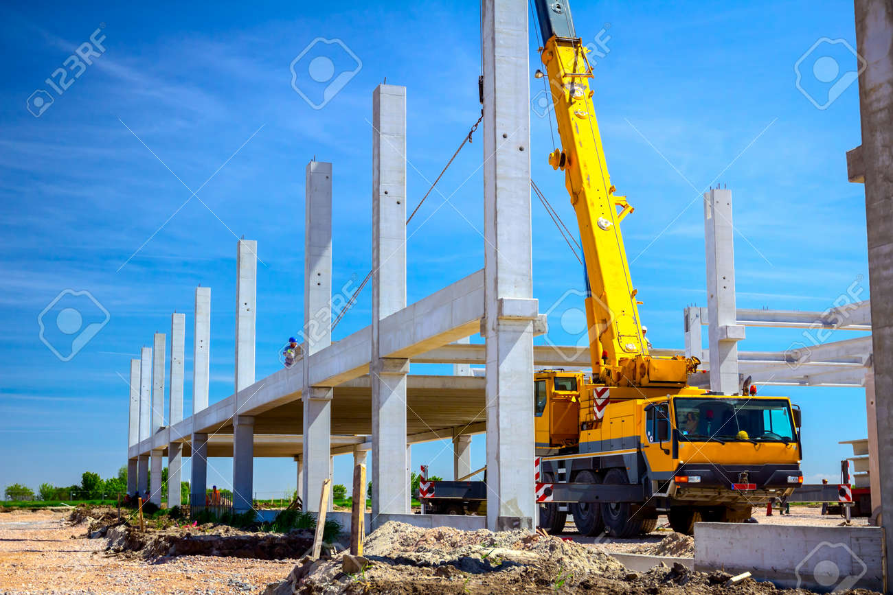 Mobile crane is operating with a huge concrete joist that hangs on chain. - 131077579