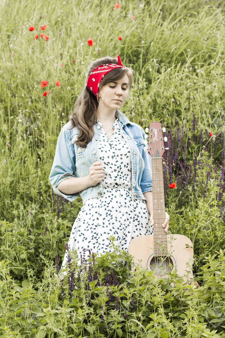 Beautiful girl with a guitar in poppies  Young woman on the grass
