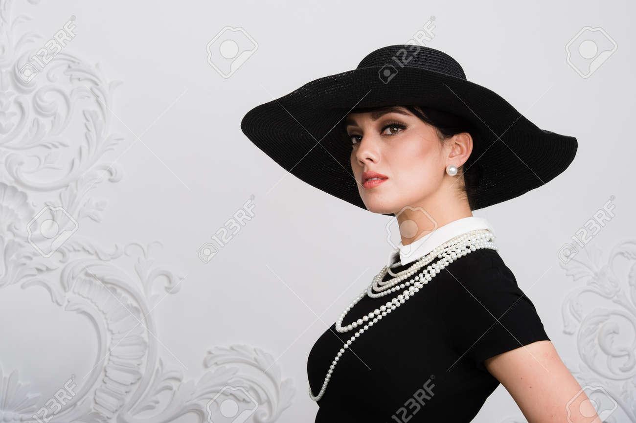 eb80a2a16da4 Archivio Fotografico - Ritratto di una bella giovane donna in stile retrò  in un elegante cappello nero e vestito su sfondo di lusso rococco muro.