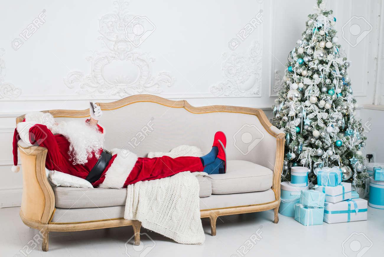 Santa Claus Resting On A Sofa At Home. Funny Santa Lying, Christmas Pause  Stock