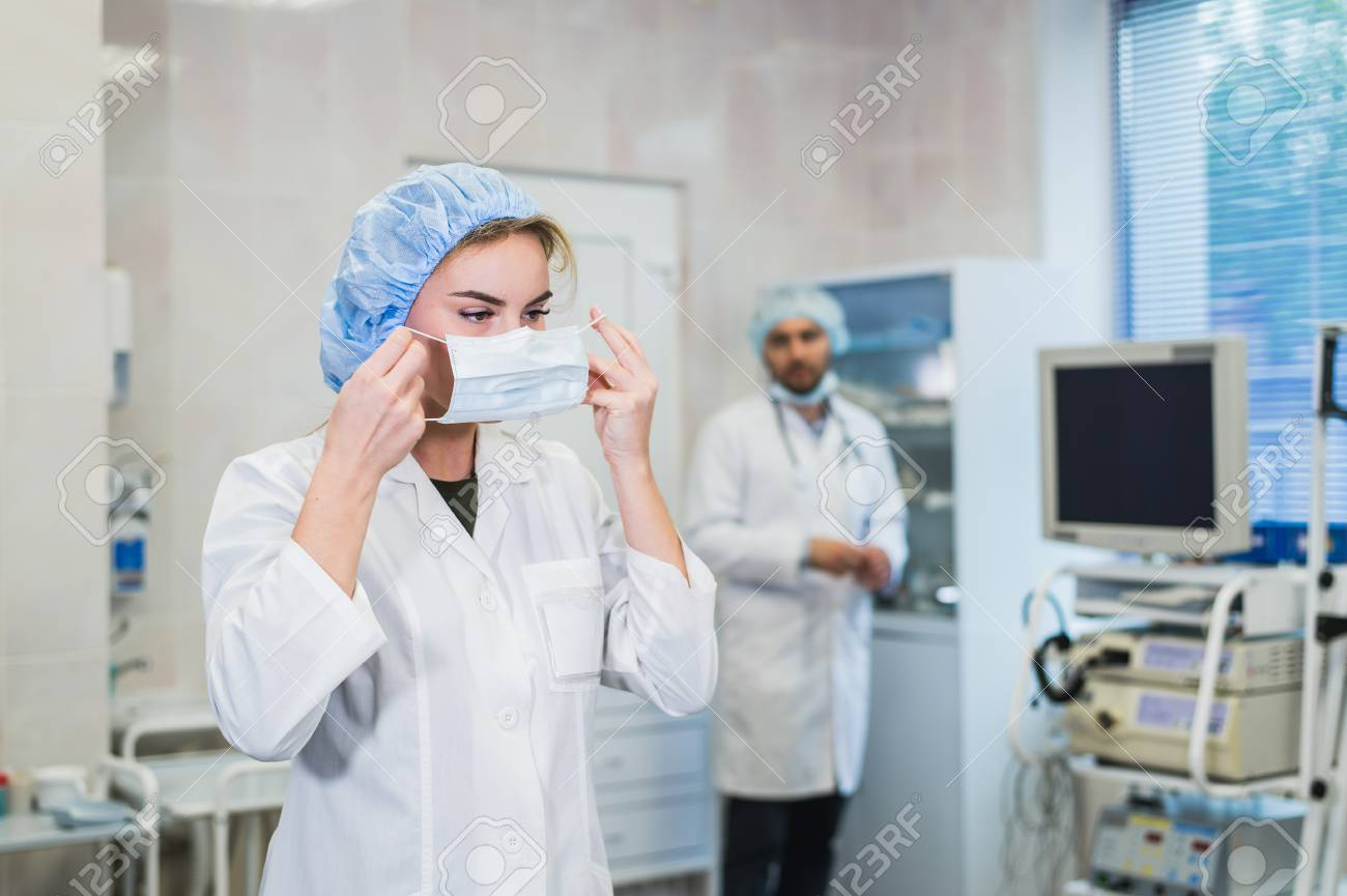 Confident female doctor putting on medical face mask while preparing for operation, her male colleague standing behind her - 83332446