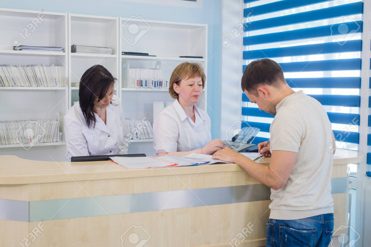 Male patient with doctor and nurse at reception desk in hospital - 97963134