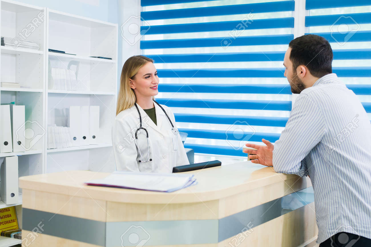 man talking to female receptionist at hospital stock photo 97963139