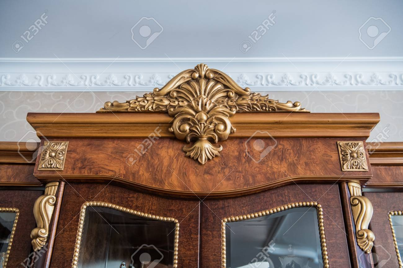 Luxury cupboard with stucco mouldings. Vintage woodworking and finishing on antique  furniture. Stock Photo - Luxury Cupboard With Stucco Mouldings. Vintage Woodworking And