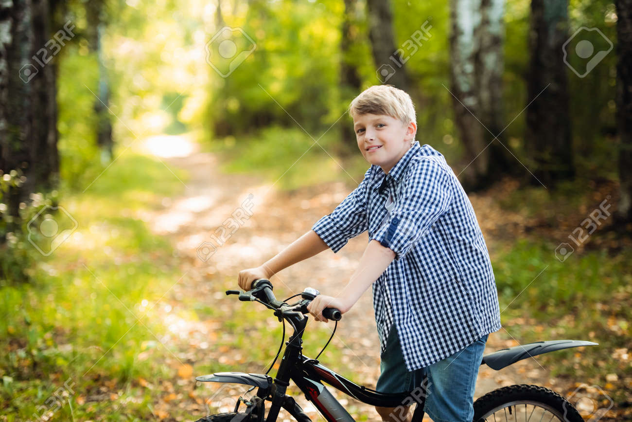 Teen boy rides a bicycle along a path in the forest. The cyclist rides fast through the springboards. - 146655956