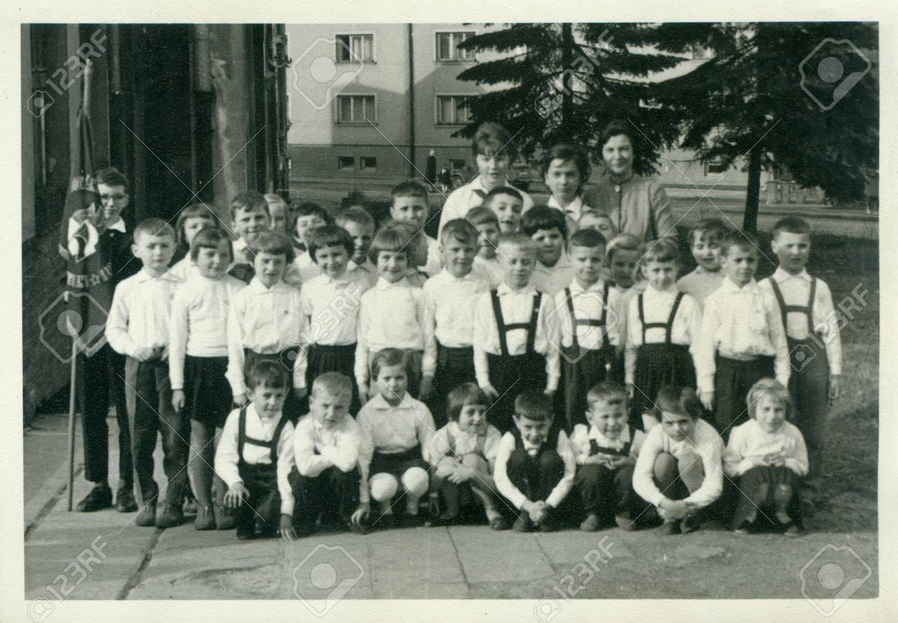 Circa 1960s retro photo shows small pupils and they female teachers schoolmistresses pose for photograper outside vintage black white photography